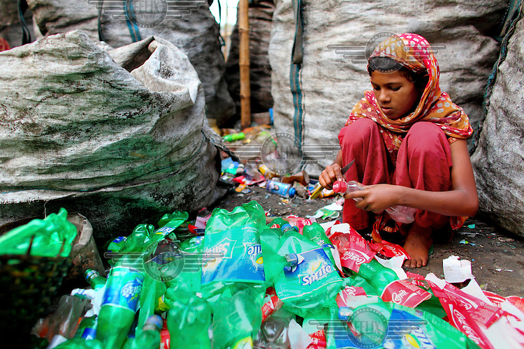 A girl, sitting among piles of plastic drinks bottles collected from Dhaka's streets, removes their labels in a factory producing PET (Polyethylene terephthalate) flakes. Bangladesh exports over 20,000 tonnes of PET flakes made in 3,000 factories located across the country in an industry worth GBP 7 million in 2010. The business is growing by 20 percent every year.