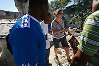 EDV staff member Emma Taylor assessing the site of a damaged orphanage with community members, Port-au-Prince, Haiti.  EDV is committed to affecting permanent change in disaster-affected communities worldwide. Their role is to facilitate personal connections between volunteers and the survivors of disasters.  The charity is based on a proven model developed by several landmark organisations that have paved the way for citizens to become disaster volunteers. These landmark organisations have shown that supposedly ordinary people working together with the guidance of knowledgeable leaders can make an extraordinary difference in the lives of those affected by disaster..EDV believe that to provide meaningful relief and reconstruction assistance to disaster affected communities they have to do more than reconstruct buildings. They need to understand and address the factors that made a community vulnerable to the disaster in the first place. The charity's work is organised with these factors in mind so that they can affect change that far outlives their presence..EDV believes that survivor motivation is essential to the recovery of any disaster-affected community. Their operations will always be predicated on the idea that survivors may be traumatised, but they are not helpless. With this in mind, EDV encourages host communities to direct their own recovery. EDV believe that this empowerment is essential in helping survivors feel a renewed sense of control over their lives which will, in turn, help overcome the feelings of hopelessness that can follow a disaster and inhibit long term recovery. EDV also believe that social cohesion is of primary importance in any disaster-affected area. No amount of bricks or mortar will bring about sustainable improvement if communities fail to come together or are disrupted by relief efforts. Therefore, their operations will always aim to foster communication and cooperation within and between the communities they serve.