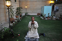 A security guard takes a moment to say his prayers in the garden of an Islamabad hotel..