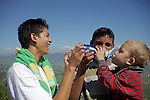 Asia, Nepal, Kathmandu. Brothers help toddler drink from water bottle.
