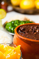 Feijoada at Bar do Mineiro, Santa Teresa district, Rio de Janeiro, Brazil - Feijoada is a stew of beans with beef and pork, which is a typical dish in Brazilian Cuisine. The Brazilian feijoada is prepared with black turtle beans, a variety of salted pork and beef products, such as pork trimmings ( ears, tail, feet ), bacon, smoked pork ribs, and at least two types of smoked sausage and jerked beef ( loin and tongue ). In Brazil, feijoada is traditionally served with rice, and accompanied by chopped fried collard greens ( couve mineira ), lightly roasted coarse cassava flour ( farofa ) and peeled and sliced orange.
