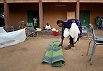 A woman rolls up the mat she slept on in a Catholic training center in Niamana, Mali. Several families displaced by the fighting in northern Mali took refuge in the center, and have received support from the ACT Alliance.