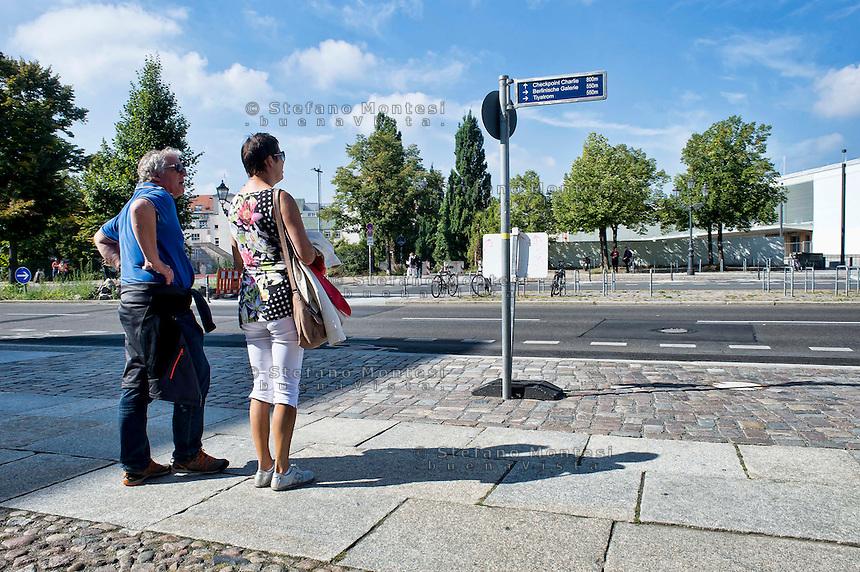 Berlino 14  Settembre 2013<br /> Turisti leggono un cartello con le indicazioni stradali<br /> Tourists read a sign with directions