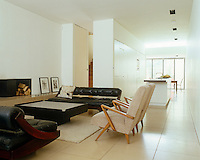 Large limestone floor tiles unify the living, kitchen and dining areas of an open-plan London house where the living room furniture is all mid-century vintage in black and beige