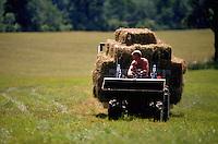 Farmer bringing in hay on a hay wagon.