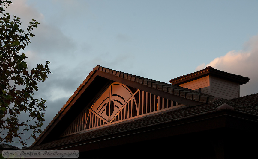 A detail view of the roof design of the restroom and storage building building at Stanton Central Park at sunset.  A cloudy sky makes up the background, with a tree providing framing.