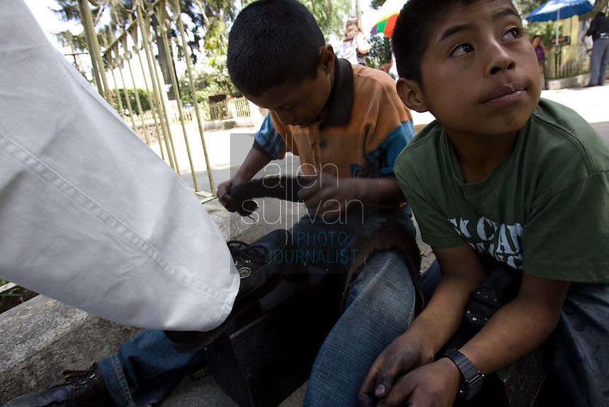 Elias (left), 9, and Armando, 11, shine shoes at the central park in Chimaltenango, Guatemala on Thursday, March 8, 2007. The boys said they work here every day and have never been to school.