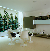 This plant-filled dining room is furnished with a Saarinen Tulip table and Knoll chairs