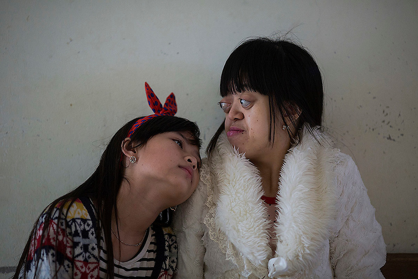 Nguyen Thi Van Long (R) and her best friend Dinh Thi Huong who is deaf and mute spend time together at the Friendship village, a hospice for Agent Orange victims outside Hanoi April 8, 2015. Fathers of both girls were soldiers exposed to the Agent Orange during the Vietnam War and health officials link their heath condition to it. Some 120 children and 60 Vietnamese veterans stay at the village that was established in 1998 by the U.S. veterans of war for children with Agent Orange relater birth defects.   REUTERS/Damir Sagolj
