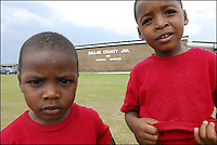 Two boys play in front of the Dallas County Jail in Brantley, Ala., where their father's are jailed on drug charges.