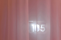 Room numbers are illuminated with an evocative use of neon lighting