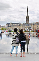 miror d'eau two young women st michel church place de la bourse bordeaux france