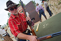Competitor picks up his gun from the weapon inspection table during the Cowboy Action Shooting European Championship in Dabas, Hungary on August 11, 2012. ATTILA VOLGYI