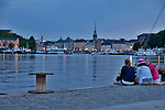 Three girls sit by the water and admire the view of the Old Town in Stockholm, Sweden