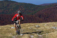 Mountain biker riding the slopes of the Tarcu Mountains Natura2000 site. Southern Carpathians, Munții Ṭarcu, Caraș-Severin, Romania.