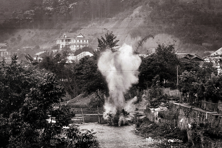 A controled explosion carried out by UXO Lao on a cluster bomb unit spotted in a river in Sam Neua, northern Laos.