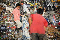 Taupik, 14, working alongside other trash pickers on the 'Trash mountain', Makassar, Sulawesi, Indonesia.