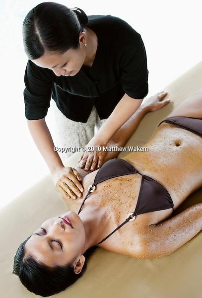 Woman receiving body scrub at Rebab Spa, Kayumanis Gangsa, Bali, Indonesia. The body scrub is part of Balinese Dream, a signature spa treatment at Rebab Spa.