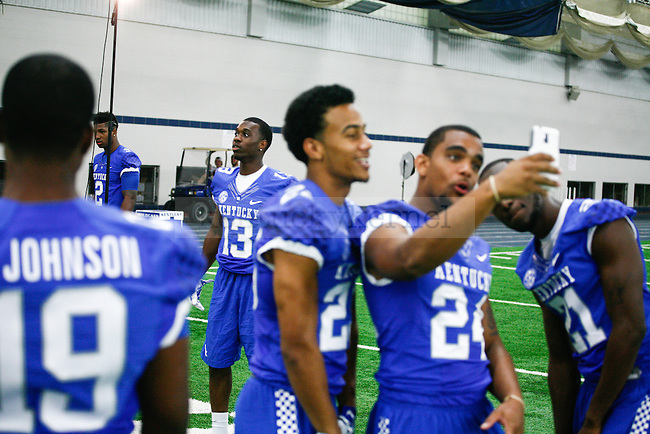 """Wide receiver Jeff Badet poses for a picture in the background while some players take a """"selfie"""" during UK football media day at Nutter Field House in Lexington, Ky., on Friday, August 8, 2014. Photo by Adam Pennavaria   Staff"""