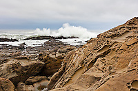 An overcast sky, a crashing wave and the tafoni sculpted rocks at Bean Hollow State Beach south of San Francisco.