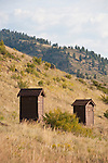 Two little brown outhouses in a campground along the Rio Grande River