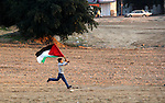 A Palestinian child holds his national flag as he runs during a rally in Gaza city on December 31, 2012. The Gaza branch of Palestinian president Mahmud Abbas's Fatah party said on Friday it will mark its anniversary in the Hamas-ruled enclave after an accord between the two factions. Photo by Ezz al-Zanoon