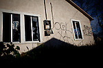 An abandoned home is vandalized and covered in gang tags in the Parklawn neighborhood in Modesto, Calif., February 22, 2012.