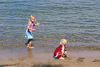 Two Children playing on a Sandy Beach at Water's Edge, without Supervision, along a West Coast Seashore (No Model Release Available)