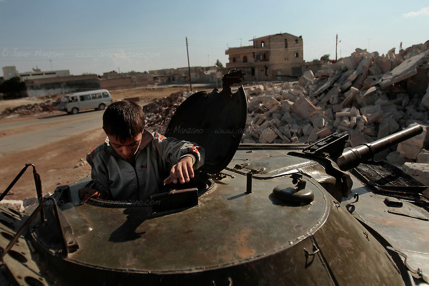 A young boy plays with the remains of a tank destroyed during heavy fighting on the northern city of Az'az on early August, 2012...© Javier Manzano