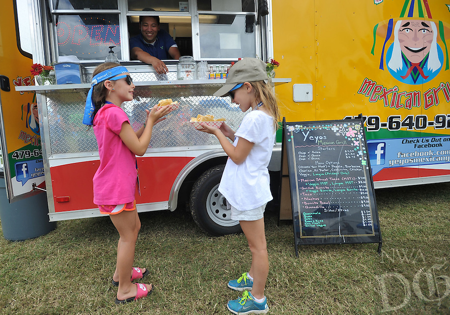 NWA Media/Michael Woods --06/27/2014-- w @NWAMICHAELW...Isabel Iuso, age 7 from Rogers, (left) and her best friend Maya Ellgass, age 7 from Rogers, pick up their nachos as owner of the Yeyo's Mexican Grill food truck, Rafael Rios, serves customers from his truck at the food truck village set up near the 17th green at the Walmart NW Arkansas Championship Presented by P&G at Pinnacle Country Club in Rogers.   Rios usually sets up at a spot in downtown Bentonville but is serving food at the LPGA tournament along with other local food trucks.
