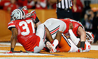 Ohio State Buckeyes defensive lineman Joey Bosa (97) and Ohio State Buckeyes linebacker Joshua Perry (37) take down Clemson Tigers quarterback Tajh Boyd (10) for a safety in the 1st quarter of their game against Clemson Tigers in the Discover Orange Bowl at Sun Life Stadium in Miami Gardens, Florida on January 3, 2014.(Dispatch photo by Kyle Robertson)