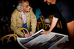 "Christo signs a poster...Conceptual artist Christo and his team attend BLM hearings regarding the artist's proposal to hang six fabric over six miles of the Arkansas River through the Bignhorn Canyon east of Salida, Colo.  The controversial proposal was put before a series of hearings to solicit comments from the public regarding the installation.  .CREDIT: ""Matt Slaby/LUCEO for The Wall Street Journal"".CHRISTO"