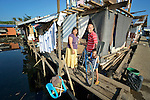 """Rachel and Rennel de la Cruz, and their son John Ray, have rebuilt a temporary shelter where their home once stood in Tacloban, a city in the Philippines province of Leyte that was hit hard by Typhoon Haiyan in November 2013. The storm was known locally as Yolanda. The dwelling is in a """"no build"""" zone declared by the Philippine government, and the family says they're hoping the government will make it possible for them to build a permanent house elsewhere."""