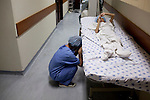 Thang's mother, Tuyet, 31, cries next to Thang before he goes into surgery for his heart defect in Ho Chi Minh City, Vietnam...---..Nguyen Van Thang is nine-years-old and just finished second grade. He lives in the coastal town of Nha Trang with his mother, grandmother, and 10-month-old brother. Thang's father, Bui Van Tri, spends much of his time away from his family, as he is a fisherman and works up and down the coastline. His income is about 400,000VND (~$23USD) per month; however, this salary is seasonal and there are months when he earns nothing at all. ..Thang's mother, Nguyen Thi Bach Tuyet, is 31-years-old and is a housewife. She cannot work as she must look after Thang, his brother, and his grandmother. Therefore, the family of five is solely dependent on Thang's father's income. The family lives in a lean-to extension of Thang's uncle's house that is just eight square meters with a tin roof, cement floor, and brick walls...Thang suffers from Ventricular Septal Defect (VSD), a common congenital heart defect (CHD) that occurs when there is a hole in the wall between the right and left ventricles of the heart. Symptoms of VSD include shortness of breath, fast heartbeats, loss of appetite, poor weight gain, chest pain, and discolored blue skin. In addition, other areas of the child's development such as physical growth and brain development are affected if VSD is left untreated, and the child also has a high chance of developing irreversible pulmonary hypertension...Thang was diagnosed with VSD when he was just two-months-old. He and Tuyet, his mother, made the arduous 10-hour trek from Nha Trang to the Heart Institute in Ho Chi Minh City at least five times over the course of his life, and the diagnosis was always the same: Surgery, or else he would die. Lifesaving surgery, however, was out of the question as it cost $3,100USD--a sum that was beyond anything Thang's family could scrape together. After each hospital visit Tuyet would make the long bus journey