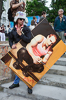 Moscow, Russia, 19/05/2012..An artist carries a painting of Russian President Vladimir Putin as several thousand artists and opposition activists demonstrate against Putin by walking through Moscow transporting their artworks. The protest coincided with Museum Night, when Moscow's museums are open until midnight with special exhibitions and performances.