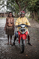 Ugala Loke, 29 years old, stands beside a motorcycle taxi driver in Jiwika village. For many years Ugala used to walk to Wamena market (the one way trip takes a whole day). Nowadays she makes money from tourists and when she needs to go to Wamena, she orders a motorbike taxi with her mobile phone.