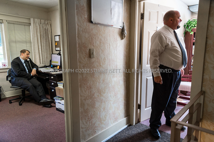 9/30/2016 -- Seattle, WA, USA<br /> <br /> <br /> Here: Undertaker James Lindley (left) working at the Columbia Funeral Home on Seattle&rsquo;s busy Rainier Avenue. Built in 1907, the home is one of the oldest in Seattle. Here Mr. Lindley is working to see if deceased indigent and homeless men are eligible for military funerals. On the right is assistant manager Roger Leger.<br /> <br /> James Lindley, 34, an undertaker and US Marine Corp Veteran, works at the Columbia Funeral Home in Seattle, Washington and has taken it upon himself to process the remains of indigent veterans and ensure their remains are placed in Tahoma National Cemetery in nearby Kent, WASH. The veterans are given full military funerals with active service members as well as volunteers who stand-in for unavailable next-of-kin, accepting the folded flags provided by the Veterans Administration.<br /> <br /> On this day, with the help of Mr. Lindley, the remains of 4 veterans were interred at the Tahoma National Cemetery: <br /> <br /> Richard Fesler, born 1951, died2014. US Army Veteran<br /> Rocky Stallone, born 1951, died 2014. Marine Corps veteran<br /> Russell Ristow, born 1944, died 2014. US Army veteran.<br /> Wayne Roberts, Born 1937, died 2014. US Navy veteran.<br /> <br /> <br /> Credit: Stuart Isett for The Wall Street Journal. <br /> VETBODIES<br /> <br /> &copy;2016 Stuart Isett. All rights reserved.