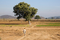 An elderly man walks through agricultural lands as children play a village game in the fields in Manikpur, Chitrakoot, Uttar Pradesh, India on 6th December 2012. Photo by Suzanne Lee for Marie Claire France.