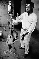 Burundi. Karuzi Province. Myogoro. The non-governmental organization (NGO) Médecins Sans Frontières (MSF) runs a suplementary feeding center where the children are weight and their height measured in order to determine if they are or not malnourished. A well-dressed young man controls the figures accurately. © 2000 Didier Ruef