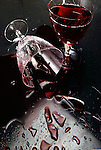 Two glasses of red wine,one glass broken and wine spreads across the table surface.