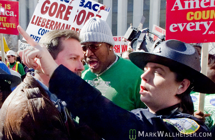 """A Florida Capitol Police Officer throws out Bush supporter from a Gore rally as the two factions collided in the Capitol plaza.  Once the Bush supporters started chanting and waving their signs, the Gore supporters, especially the AFL-CIO teamsters moved immediately to block the """"disruption"""" untill law enforcement seperated to two factions arguing over the presidential voting differences in Tallahassee, Florida December 5, 2000."""