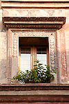 A window of a building covered in frescos in Mantua, Italy.