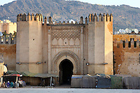 General view of Bab el-Mahrouk gate, 12th century, Fez, Morocco, pictured on February 25, 2009 in the morning.  Bab el-Mahrouk is the main gateway between the old medina and newer suburbs. Its restored stonework is seen against the mountains with market stalls in the foreground. Fez, Morocco's second largest city, and one of the four imperial cities, was founded in 789 by Idris I on the banks of the River Fez. The oldest university in the world is here and the city is still the Moroccan cultural and spiritual centre. Fez has three sectors: the oldest part, the walled city of Fes-el-Bali, houses Morocco's largest medina and is a UNESCO World Heritage Site;  Fes-el-Jedid was founded in 1244 as a new capital by the Merenid dynasty, and contains the Mellah, or Jewish quarter; Ville Nouvelle was built by the French who took over most of Morocco in 1912 and transferred the capital to Rabat. Picture by Manuel Cohen.