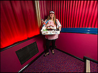 BNPS.co.uk (01202 558833)<br /> Pic: PhilYeomans/BNPS<br /> <br /> Andy's wife Jane even joins in as an usherette.<br /> <br /> Field of Dreams....<br /> <br /> Film buff Andy Jones has built an ABC cinema in his back garden as a lasting tribute to the now defunct movie company.<br /> <br /> Andy, 38, has taken four and a half years and spent &pound;70,000 of his life savings building the 34-seat cinema from scratch.<br /> <br /> The father-of-two's movie house mirrors cinemas of the 1930s with big red curtains, red seats and a parquet floor in the projection room. <br /> <br /> The brick building, which is adorned with an ABC sign, is 40ft tall, 22ft wide and 20ft high and takes up half of the garden of his three bed semi-detached house.<br /> <br /> The theatre, which has a 17ft by 7ft screen, has its own projection room, black and white old-style toilets and a foyer with a concessions stand that offers popcorn and sweets.