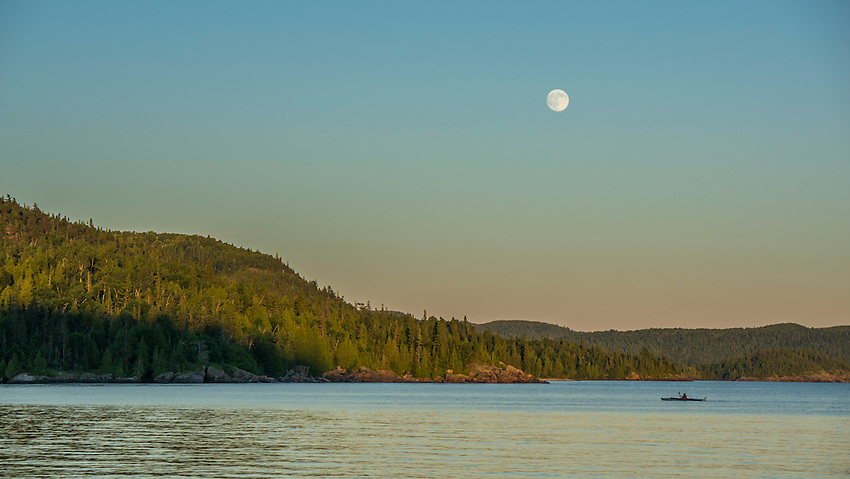 A full moon rises over a kayaker on Warp Bay at Lake Superior Provincial Park, Ontario, Canada.