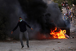 A Palestinian protester throws stones towards Israeli security forces during clashes over the Al-Aqsa mosque compound, close to the Israeli manned checkpoint of Hezma in the Israeli occupied West Bank, between Jerusalem and and the Palestinian city of Ramallah on September 30, 2015. The compound has been the scene of repeated clashes in recent weeks, provoking international calls for calm at the highly sensitive site which is the third holiest in Islam but is also known to Jews as the Temple Mount, the most sacred in Judaism. Photo by Shadi Hatem