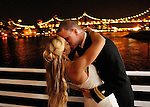 The newly weds embrace on the deck of the Water's Edge restaurant, on the banks of the East River.  They are backed by the glowing 59th street bridge and the Manhattan skyline.