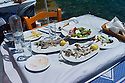 Santorini, Greece. 06.05.2014. A finished meal of locally caught fish on a table at a restaurant in Ammoudi, which is at the foot of the cliffs, below the town of Oia, at the northern tip of the island. Photograph © Jane Hobson.