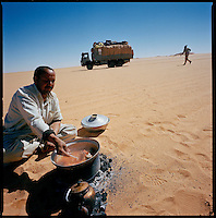 Sahara desert, Libya-Chad, November/December 2004..Every week, a convoy of 40 privately owned Libyan trucks loaded by the WFP with about 1000 metric tons of western food aid cross 2500 km of deep desert across Libya and Chad to reach more than 200 000 refugees from Darfur in camps near the Sudanese border. Moussa prepares lunch: mutton and pasta...the menu is always the same, every day, lunch and supper...