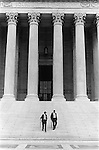 "WASHINGTON DC - USA 1969 EQUAL JUSTICE UNDER LAW. TWO IDENTICALLY DRESSED MEN IN BUSINESS SUITS AND CARRYING ROLLED UMBRELLAS WALK DOWN  ""Equal justice under law"" is a phrase engraved on the front of the United States Supreme Court building in Washington D.CBUI."